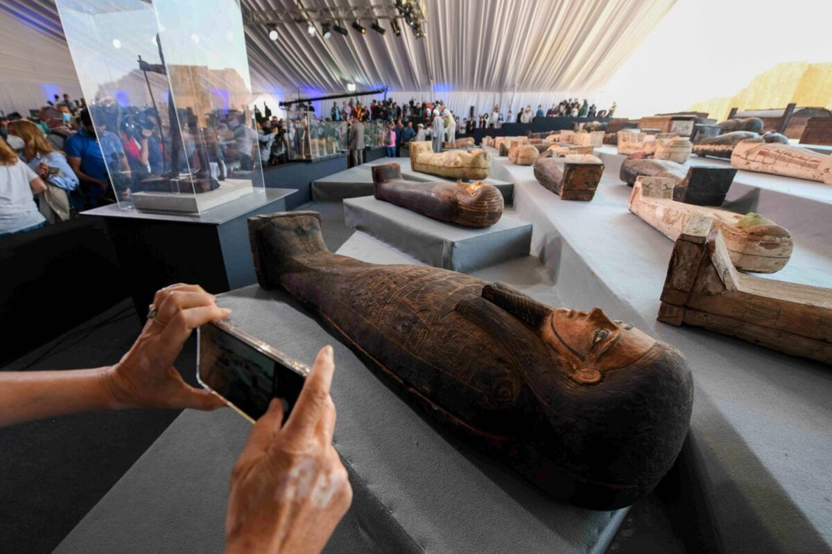 A picture shows wooden sarcophagi on display during the unveiling of an ancient treasure trove of more than a 100 intact sarcophagi, at the Saqqara necropolis 30 kms south of the Egyptian capital Cairo, on November 14, 2020. - Egypt announced the discovery of an ancient treasure trove of more than a 100 intact sarcophagi, the largest such find this year. The sealed wooden coffins, unveiled on site amid fanfare, belonged to top officials of the Late Period and the Ptolemaic period of ancient Egypt. They were found in three burial shafts at depths of 12 metres (40 feet) in the sweeping Saqqara necropolis south of Cairo. (Photo by Ahmed HASAN / AFP) (Photo by AHMED HASAN/AFP via Getty Images)