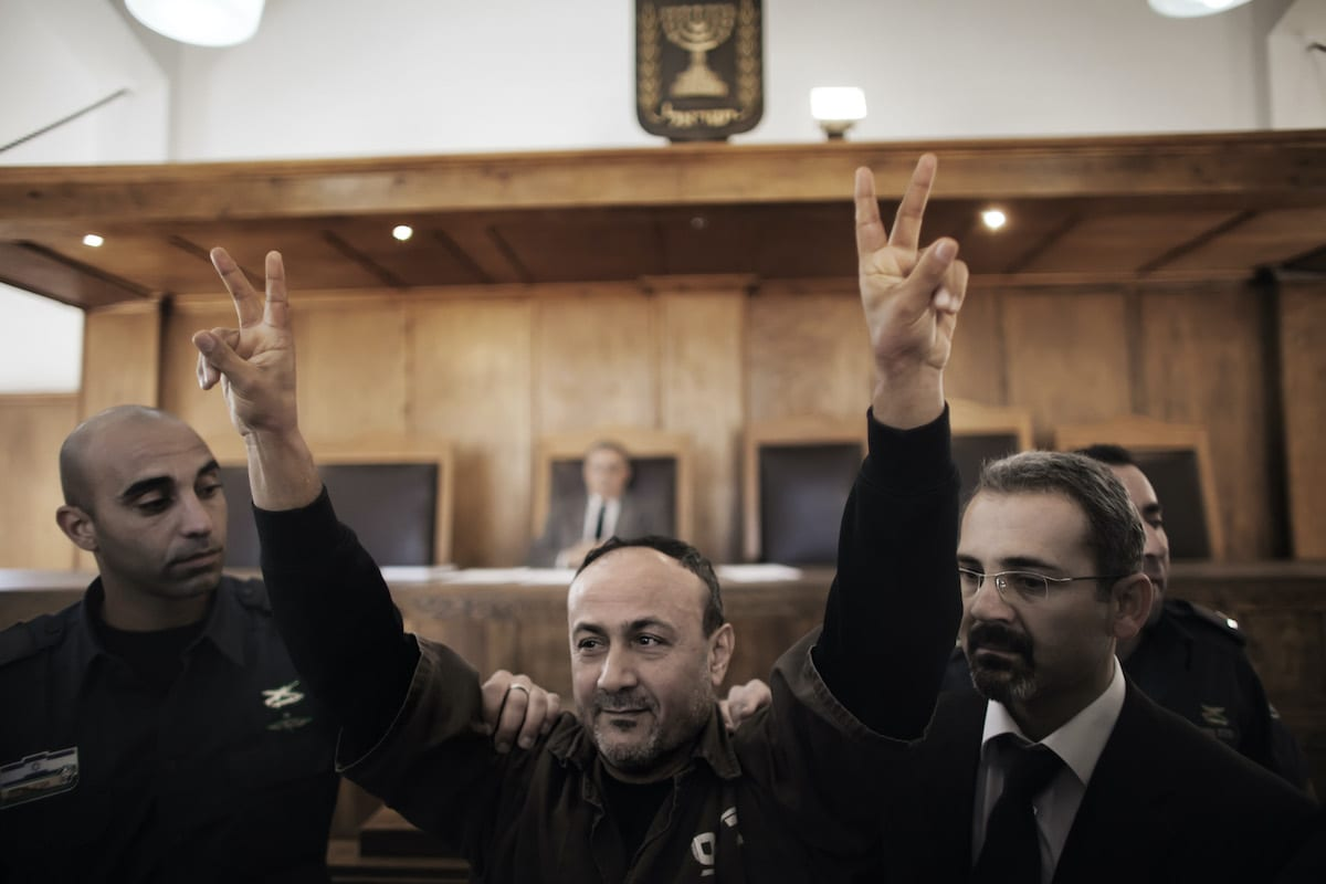 Palestinian Fatah leader Marwan Barghuti flashes the V-sign of victory as he is escorted by Israeli police into Jerusalem's Magistrate Court to testify as part of a US civil lawsuit against the Palestinian leadership, on 25 January 2012. [MARCO LONGARI/AFP via Getty Images]