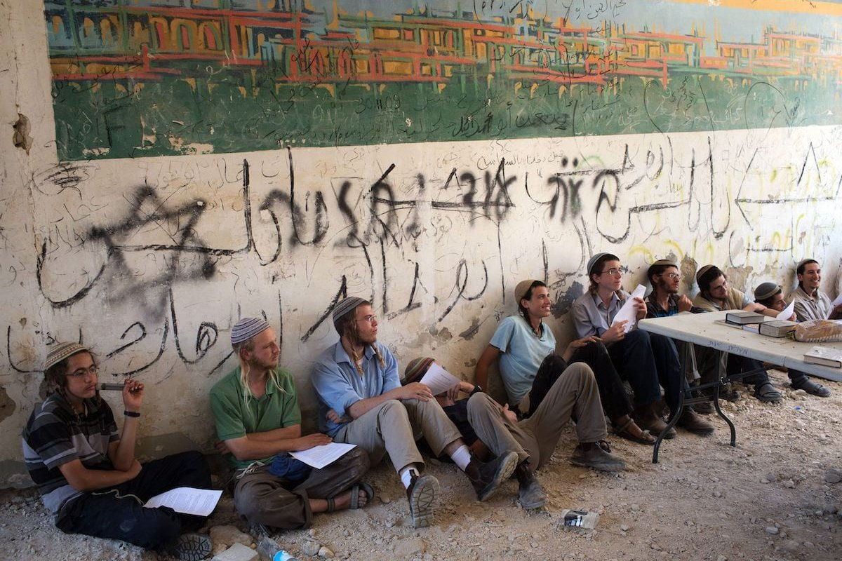 Israeli settlers sit in the former Sanur settlement in the northern West Bank, which was evacuated by Israel in 2005, after some 200 settlers illegally entered the place, on 28 July 2015. [MENAHEM KAHANA/AFP via Getty Images]