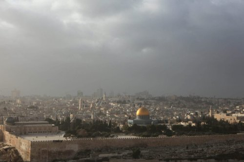 A ray of light hits the Dome of the Rock Mosque as a dust storm covers the Jerusalem skyline on December 17, 2009 [GALI TIBBON/AFP via Getty Images]