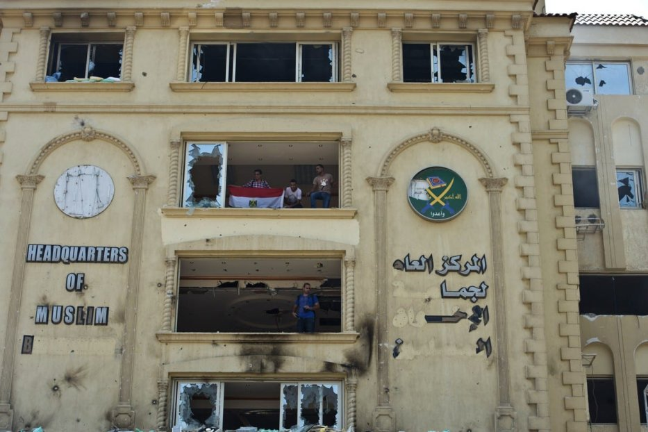 Egyptian protesters stand in the burnt headquarters of the Muslim Brotherhood in Cairo, Egypt on 1 July 2013 [KHALED DESOUKI/AFP/Getty Images]