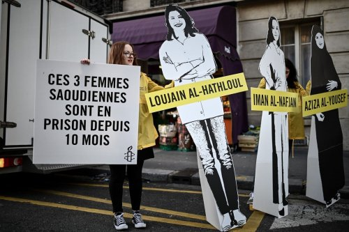 People hold signs and cartoon cutouts of women incarcerated in Saudi Arabia during a demonstration outside the Saudi Arabia embassy in France on 8 March 2019 [PHILIPPE LOPEZ/AFP/Getty Images]