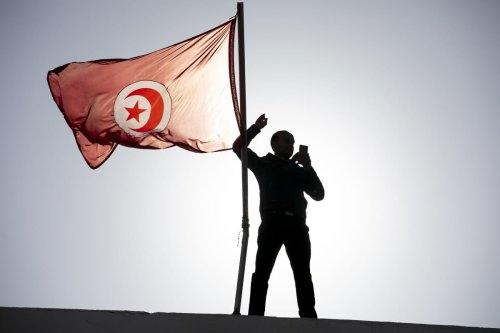 A man is seen next to a Tunisian flag as people stage a protest on the call of the Tunisian General Workers Union (UGTT) in Kairouan, Tunisia on December 03, 2020 [Yassine Gaidi / Anadolu Agency]