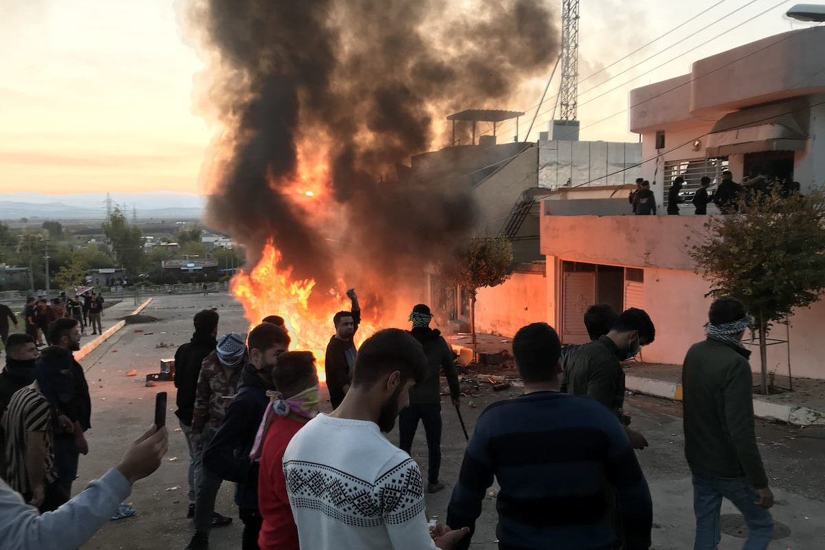 Smoke rises after protesters set fire to some political party buildings and government offices in Seyitsadik district during protests due to salary delays in Sulaymaniyah, Iraq on December 7, 2020 [Fariq Faraj Mahmood/Anadolu Agency]