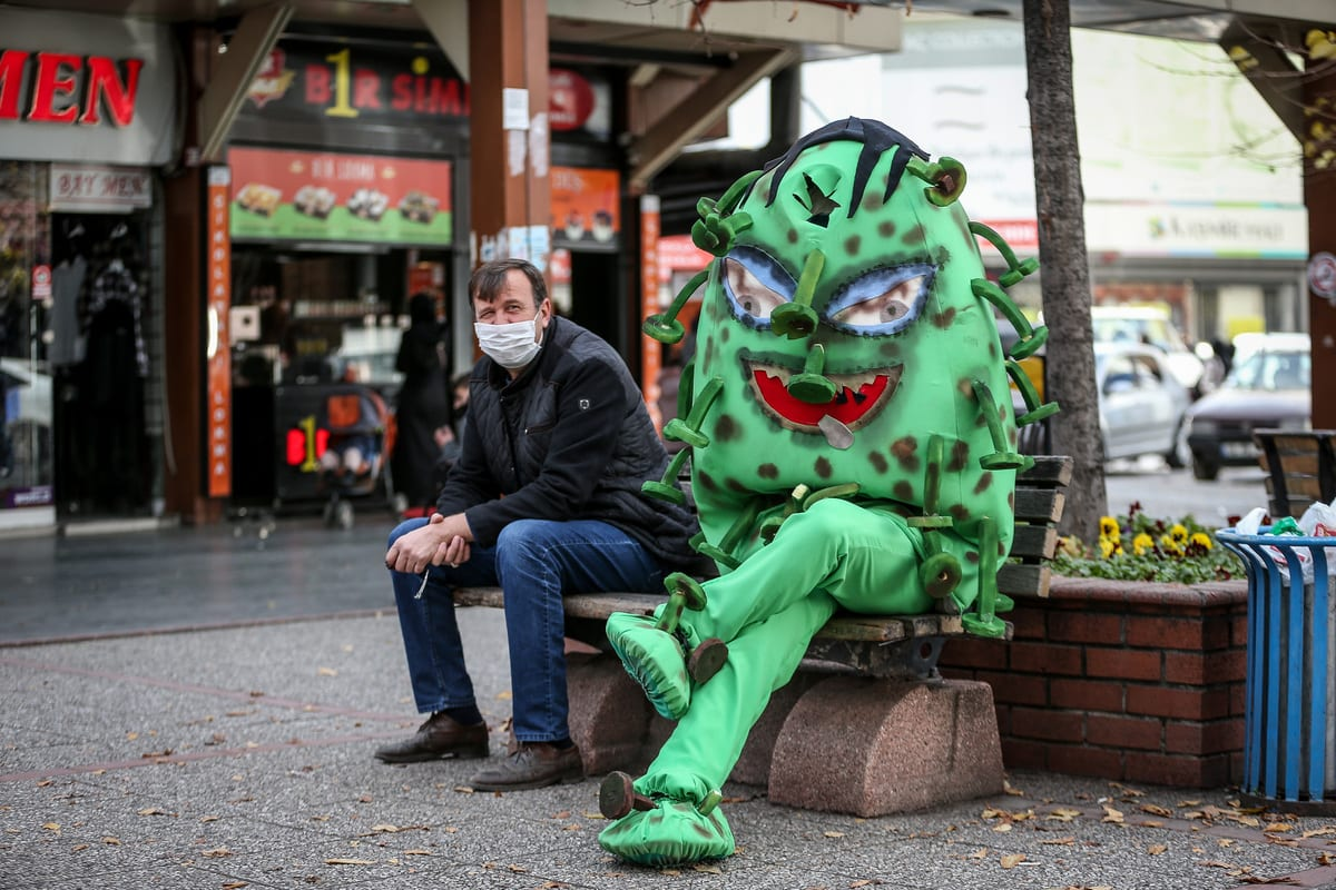 A municipality staff wearing a Covid-19 costume, shaped like green colored globe, warn people walking around in the streets on 10 December 2020 in Inegol district of Bursa, Turkey. [Sergen Sezgin - Anadolu Agency]