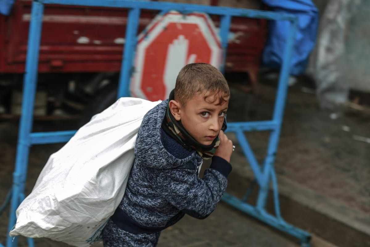 A boy carries a sack as workers of United Nations Palestine Refugee Agency (UNRWA) package humanitarian aid in Jabalia, Gaza on December 17, 2020 [Ali Jadallah/Anadolu Agency]