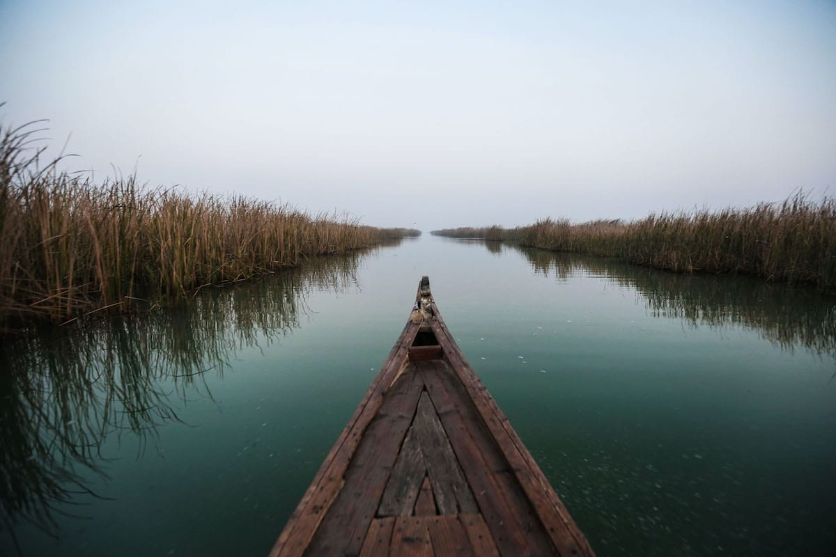 NASIRIYAH, IRAK - DECEMBER 24: A fishing boat gliding through the yellowish reeds in the Mesopotamian Marshes, also known as the Iraqi Marshes, which is a wetland area located in Southern Iraq and Southwestern Iran, in Nasiriyah, Iraq on December 24, 2020 [Murtadha Al-Sudani / Anadolu Agency]