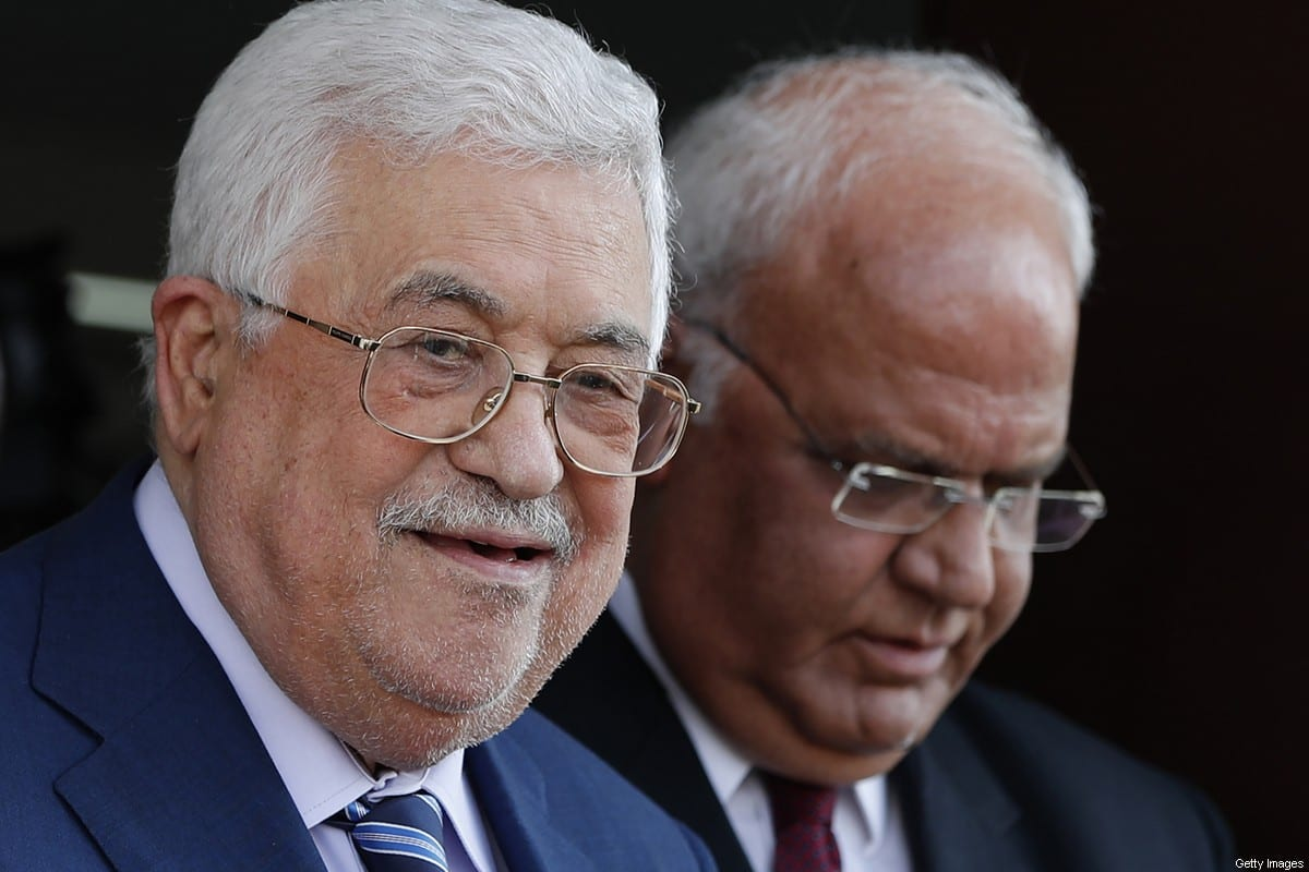 Palestinian President Mahmoud Abbas (L) walks with Palestine Liberation Organisation secretary-general Saeb Erekat during their visit to the Pilgrims City, in the West Bank town of Jericho on August 6, 2018. [AHMAD GHARABLI/AFP via Getty Images]