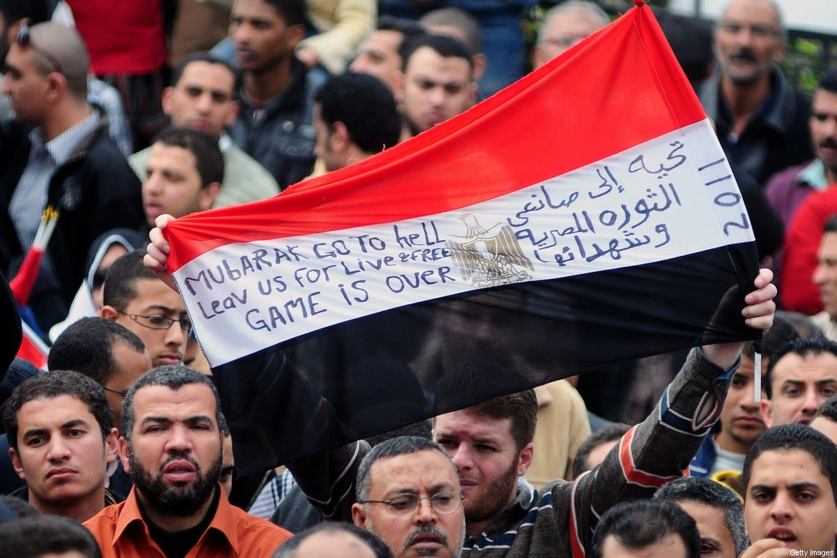 "An Egyptian anti-government demonstrator holds his national flag bearing the writing in Arabic ""A salute to the makers of the Egyptian revolution and its martyrs"" as they gather in Alexandria on February 6, 2011 on the 13th day of protests calling for the ouster of President Hosni Mubarak. AFP PHOTO/STR (Photo credit should read -/AFP via Getty Images)"