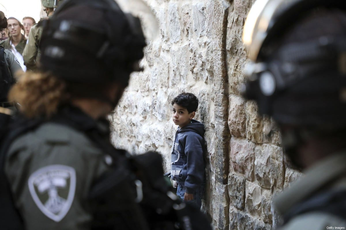 Israeli soldiers look at a Palestinian boy as he waits by the wall for Israeli settlers touring the old city and market of Hebron in the occupied West Bank to pass, on December 21, 2019. (Photo by HAZEM BADER / AFP) (Photo by HAZEM BADER/AFP via Getty Images)