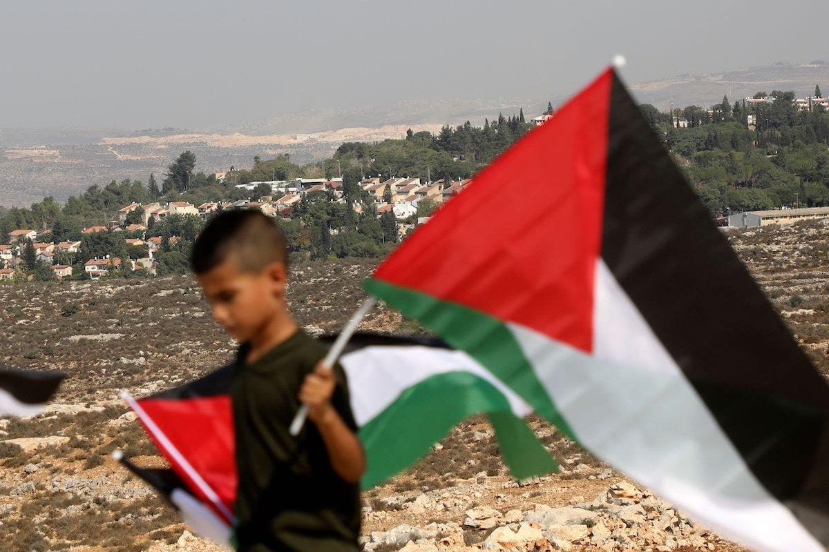 A Palestinians boy carries a national flags as he takes part in protest against an Israeli order to stop the building of a playing ground for the disabled in the occupied-West Bank town of Salfit, near the Israeli settlement of Ariel, on 28 October 2020. [JAAFAR ASHTIYEH/AFP via Getty Images]