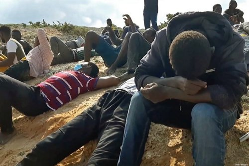 A video grab shows migrant survivors of a deadly shipwreck siting on a sandy beach on the coast of al-Khums, a port city 120 kilometres (75 miles) west of the Libyan capital Tripoli, on 12 November 2020. [AFP via Getty Images]