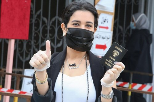 A Kuwaiti woman, wearing a protective mask and gloves amid the COVID-19 pandemic, reacts as she arrives to cast her vote at a polling station in Kuwait City during parliamentary elections on December 5, 2020 [YASSER AL-ZAYYAT/AFP via Getty Images]