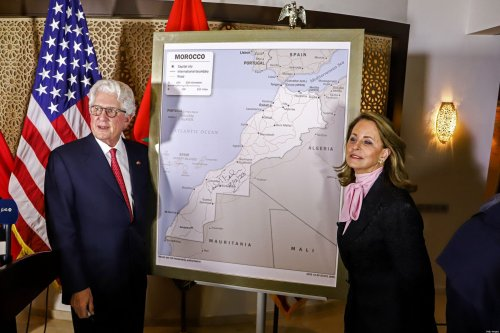 David T. Fischer (L), US Ambassador to the Kingdom of Morocco, and his wife Jennifer (R) stand before a US State Department-authorised map of Morocco recognising the internationally-disputed territory of the Western Sahara (bearing a signature by Fischer) as a part of the North African kingdom, in Morocco's capital Rabat on December 12, 2020 [-/AFP via Getty Images]