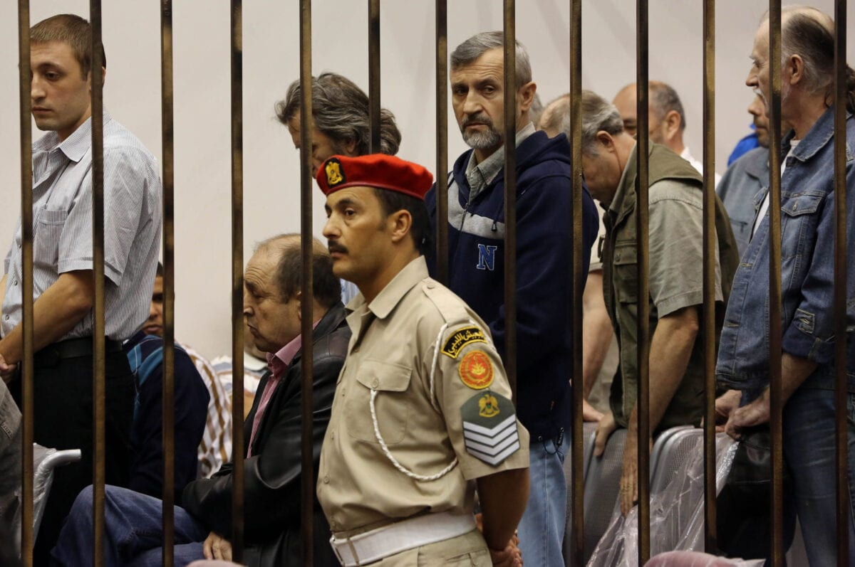 Prisoners from Belarus, Russia and Ukraine stand behind bars during their appeal trial as they are accused of serving as mercenaries for the ousted Libyan leader Moamer Kadhafi on May 29, 2013 at the Military High Court in Tripoli, Libya. 19 Ukrainians, three nationals from Belarus and two Russians have been held on charges of assisting the former regime, one was sentenced to life imprisonment, while the others received ten years in prison with hard labor in June 2012. The trial was adjourned to June 26, 2013 said the president of the military court, acceding to the request of prosecutors and defense lawyers. AFP PHOTO MAHMUD TURKIA (Photo credit should read MAHMUD TURKIA/AFP via Getty Images)