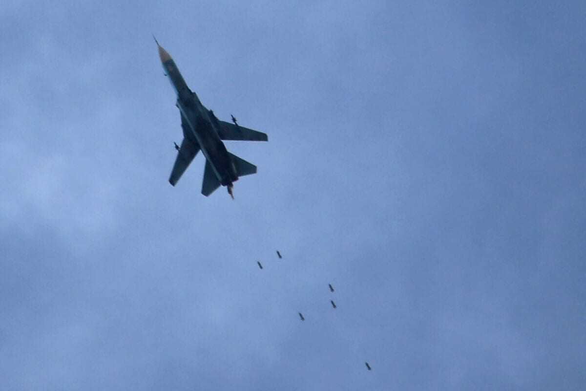 A Syrian air force MiG-23 fighter jet seen dropping a payload during an air strike in the rebel-held town of Arbin, in the besieged Eastern Ghouta region on the outskirts of the capital Damascus, on February 7, 2018 [AMER ALMOHIBANY/AFP via Getty Images]