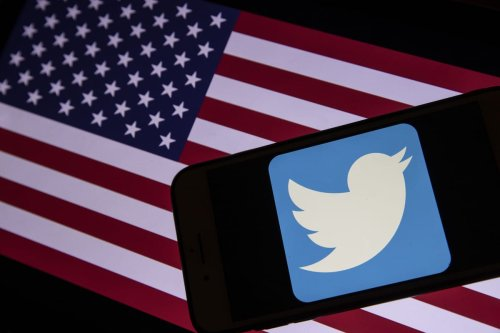 Twitter logo and a computer screen displaying the flag of the United States in Ankara, Turkey on 7 January 2021 [Erçin Ertürk/Anadolu Agency]