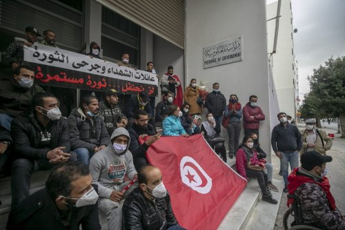 A group of Tunisians stage a protest demanding that the names of those who lost their lives in mass public demonstrations on January 14, 2011 that overthrew Former President of Tunisia Zine El Abidine Ben Ali, be added to the list of martyrs during 10th anniversary of Tunisian Revolution in Tunis, Tunisia on January 14, 2021 [Yassine Gaidi / Anadolu Agency]