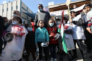 Palestinians in Gaza protest outside UNRWA's headquarters against the organisation's plans to reduce services to refugees because of its budget deficit, on 11 January 2021 in Gaza [Mohammed Asad/Middle East Monitor]