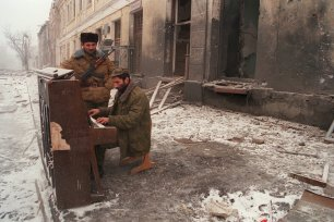 A Chechen separatist fighter plays piano 27 December 1994 in Grozny, Russia [OLEG NIKISHIN/AFP/Getty Images]