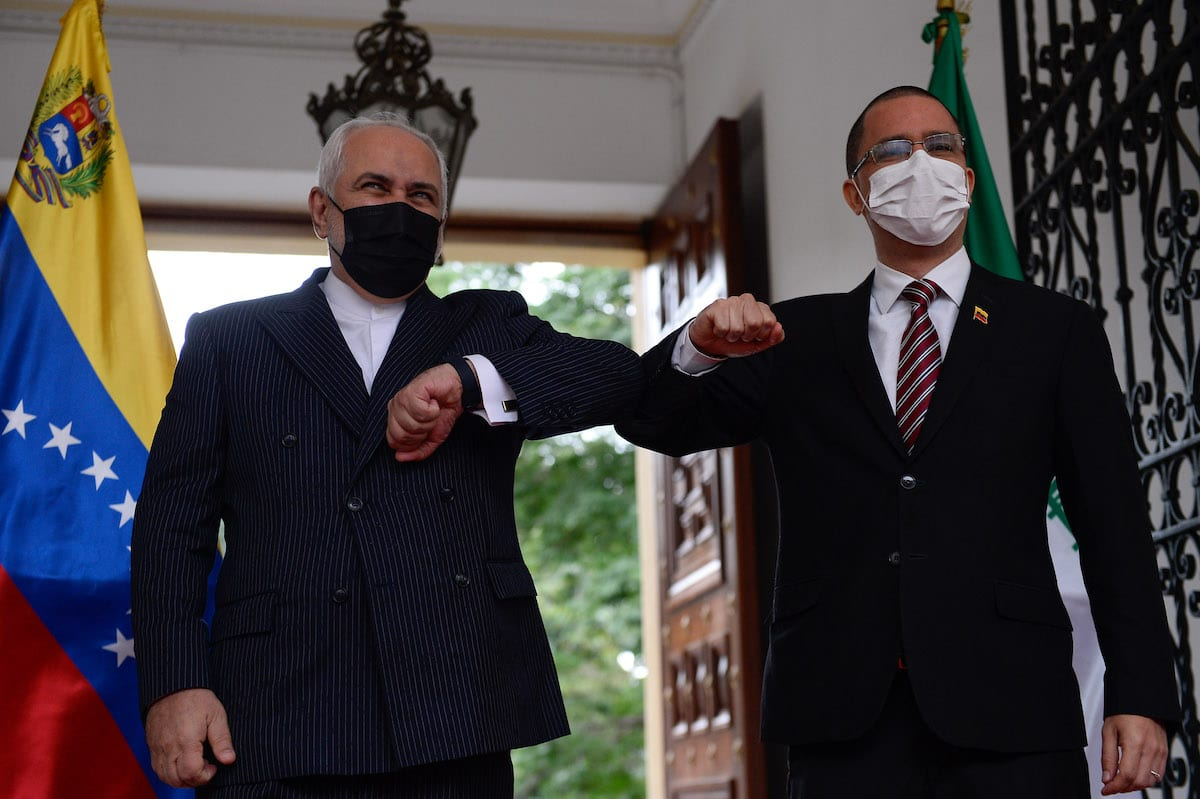 The Foreign Minister of the Islamic Republic of Iran, Javad Zarif (L), bumps elbows with Venezuelan Foreign Minister Jorge Arreaza (R), at the Casa Amarilla palace in Caracas, on 5 November 2020. [CRISTIAN HERNANDEZ/AFP via Getty Images]
