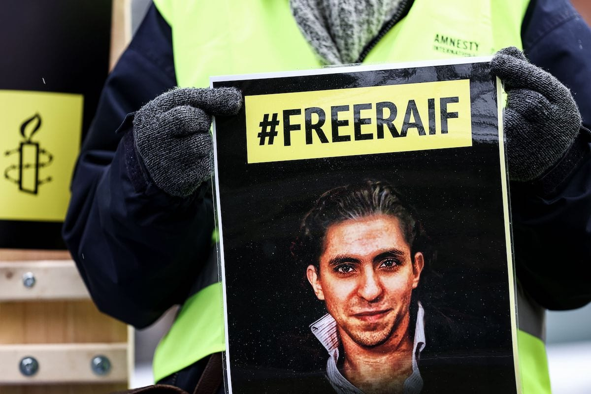 An activist of the human rights NGO Amnesty International holds a portrait of Raif Badawi in front of the embassy of Saudi Arabia in Brussels on 8 January 2021, calling for the release of the jailed Saudi blogger. - [KENZO TRIBOUILLARD/AFP via Getty Images]