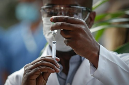 A healthcare worker prepares a dose of the Astrazeneca/Oxford vaccines at the Osvaldo Cruz Foundation (FIOCRUZ) on 23 January 2021 in Rio de Janeiro, Brazil. [Andre Coelho/Getty Images]