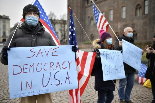 "People wearing protective mask waving the American flags and holding a protest signs that reads ""Trump Go Home"" and ""Save democracy in USA"" at Piazza Castello on January 09, 2021 in Turin, Italy [Stefano Guidi/Getty Images]"