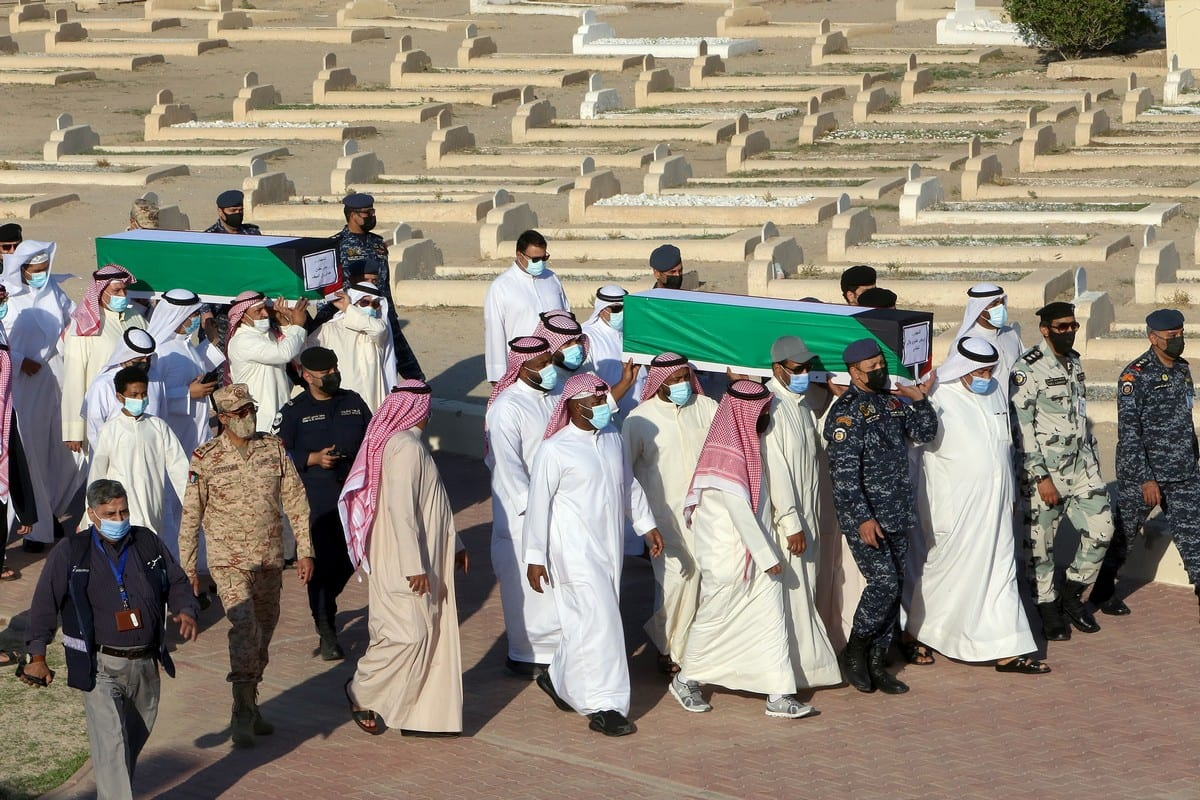 Families carry the coffins of Kuwaiti prisoners of war whose remains were found in a mass grave in Iraq and identified following a DNA test in Kuwait City on 23 November 2020 [YASSER AL-ZAYYAT/AFP/Getty Images]