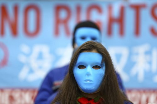 Protesters wear masks during a protest held by Team Todenhofer against the Chinese government's policies and oppressions towards Uyghurs in front of Chinese Embassy in Berlin, Germany on January 23, 2021 [Abdulhamid Hoşbaş / Anadolu Agency]