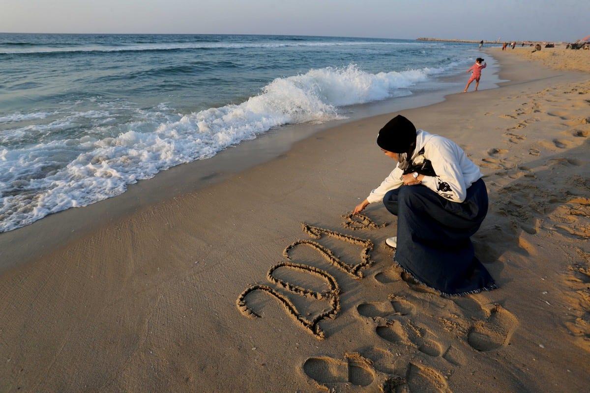 A Gazan woman writes 2021 on the sand in a Beach in Gaza on 31 December 2020 [Ashraf Amra/Anadolu Agency]