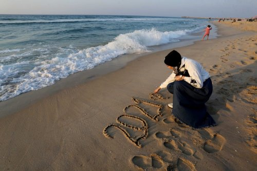 A Gazan woman writes 2021 on the sand in a Beach in Gaza on 31 December 2020 [Ashraf Amra/Anadolu Agency]