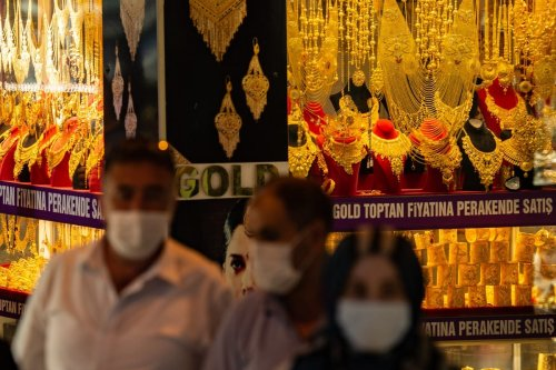 People walk past a gold shop windows in Istanbul, Turkey on 19 July 2020 [YASIN AKGUL/AFP/Getty Images]