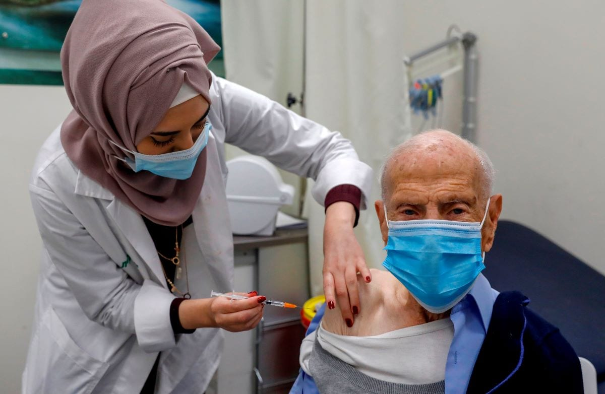 A healthcare worker administers a COVID-19 vaccine to an elderly Palestinian man at the Clalit Health Services in east Jerusalem, on January 7, 2021 [AHMAD GHARABLI/AFP via Getty Images]