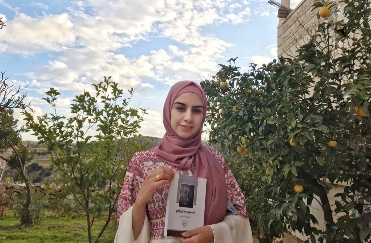 Manar Khalawi holds Osama Al-Ashqar's first book, October 2020 [Manar Khalawi/MEMO]