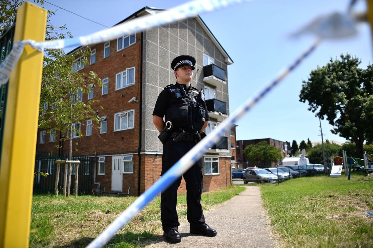 A police officer stands guard outside a cordoned off block of flats where the suspect of a multiple stabbing incident lived in Reading, west of London, on June 23, 2020 [BEN STANSALL/AFP via Getty Images]