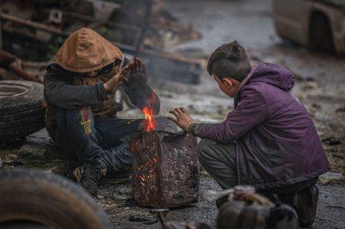 Syrian children huddle around a fire during winter season in Idlib, Syria on 30 January 2021 [Muhammed Said/Anadolu Agency]