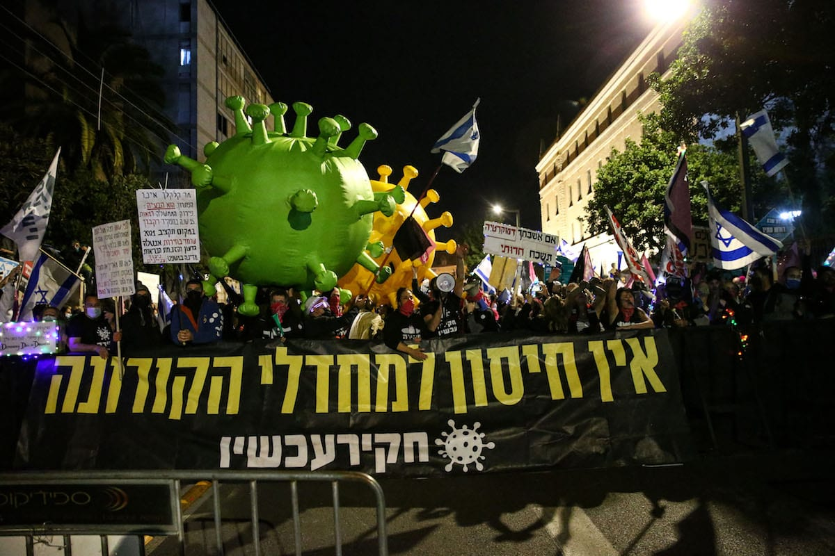 JERUSALEM - FEBRUARY 13: People holding banners gather to protest against the Israeli Prime Minister Benjamin Netanyahu for his failure to combat the novel coronavirus (COVID-19) pandemic and his corruption charge cases by demanding his resignation, outside the Prime Minister's office in Western Jerusalem on February 13, 2021. ( Mostafa Alkharouf - Anadolu Agency )