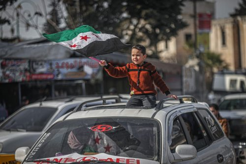 Syrian civilians holding banners and flags gather to protest to be able to return their home in Idlib, Syria on 19 February 2021. [Muhammed Said - Anadolu Agency]