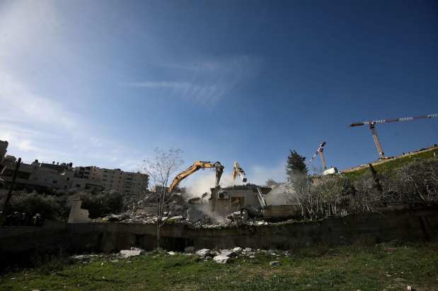 A view of the site as the Israeli-run Jerusalem Municipality team along with Israeli police and bulldozers demolishing the two-story apartment building owned by Fadi Ali Oleyyan, the head of the security department at the Al-Aqsa Mosque, near the al-Issawiya neighborhood claiming that it was unlicensed, in East Jerusalem on February 22, 2021. ( Mostafa Alkharouf - Anadolu Agency )