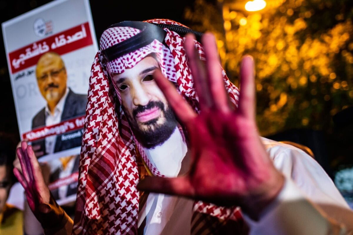 A protestor wears a mask of depicting Saudi Crown Prince Mohammad Bin Salman with red painted hands next to people holding posters of Saudi journalist Jamal Khashogg on October 25, 2018 [YASIN AKGUL/AFP via Getty Images]