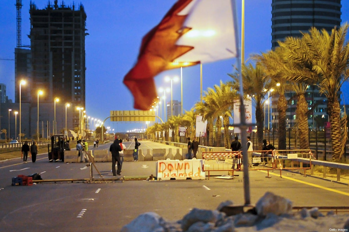 Bahraini flag seen during an anti-government protesters place concrete roadblocks on the highway leading to Pearl Square in Manama on March 14, 2011 [JAMES LAWLER DUGGAN/AFP via Getty Images]