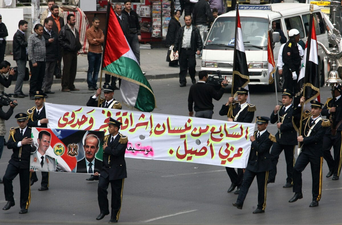 Members of a Syrian military band hold a poster showing Syrian President Bashar al-Assad (L) and his late father and predecessor Hafez al-Assad during a parade marking the anniversary of the Baath party in Damascus on April 7, 2011 [AFP via Getty Images]