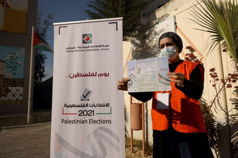 A Palestinian member of Central Elections Commission displays an information leaflet following the opening of the first Voter Information and Registration Centre in Gaza City on 10 February 2021. [MOHAMMED ABED/AFP via Getty Images]