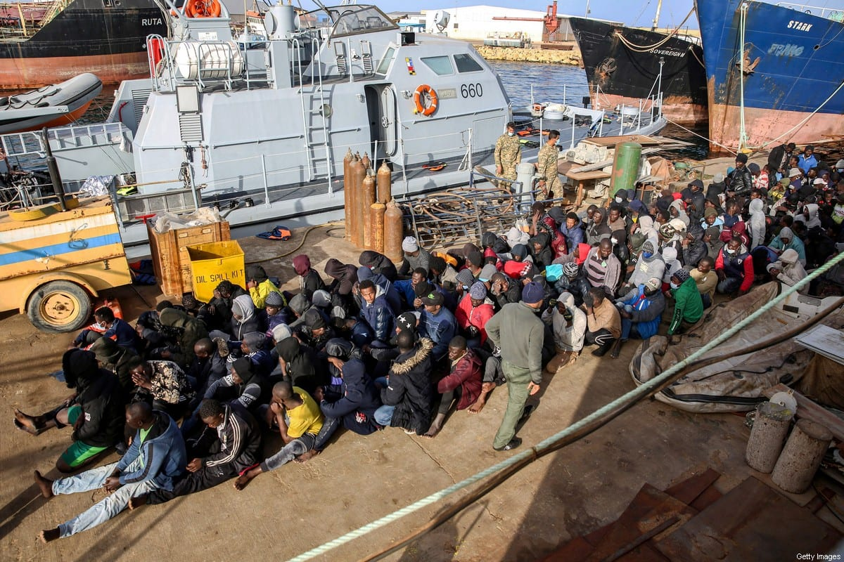 Migrants rescued off the coast of Al-Khums, about 120 kilometres east of the capital, sit on the pier in Tripoli's naval base on February 10, 2021 [AFP via Getty Images]