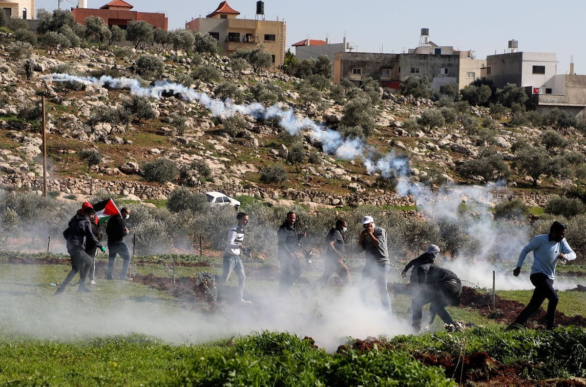 Israeli security forces fire tear gas to disperse Palestinian protesters following a demonstration against the expansion of settlements near the village of Beit Dajan, east of Nablus, in the occupied West Bank, on 12 February 2021. [JAAFAR ASHTIYEH/AFP via Getty Images]