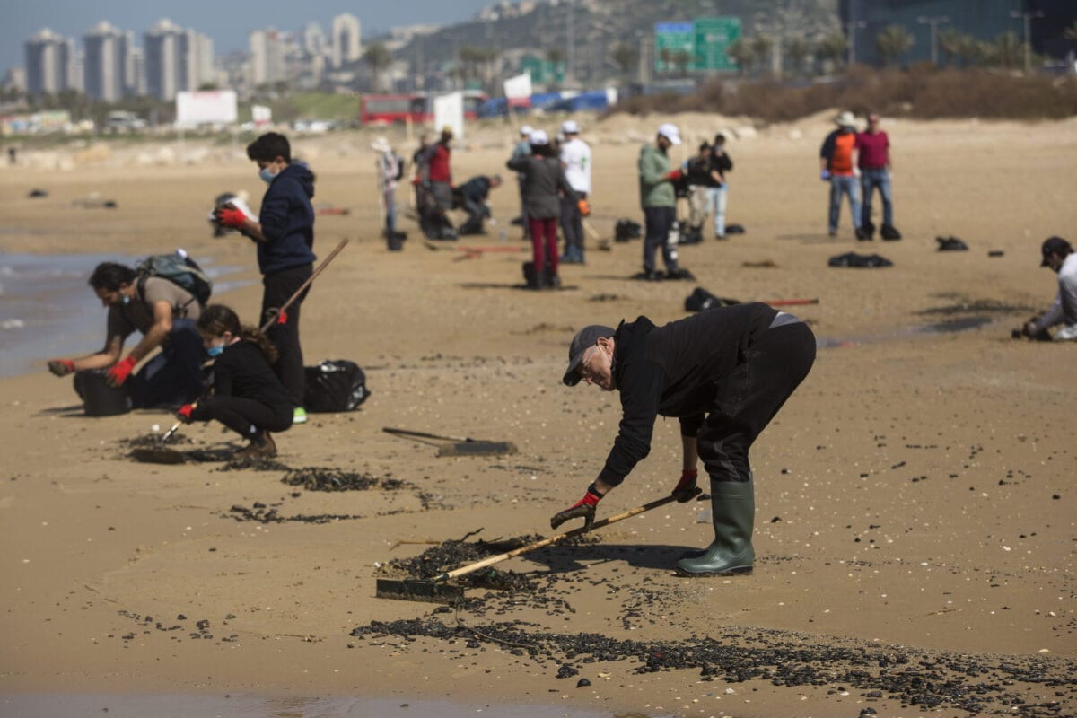 Israelis clean tar from the sand after a suspected oil spill off covered Israel's coast with tar on February 25, 2021 in Haifa, Israel [Amir Levy/Getty Images]