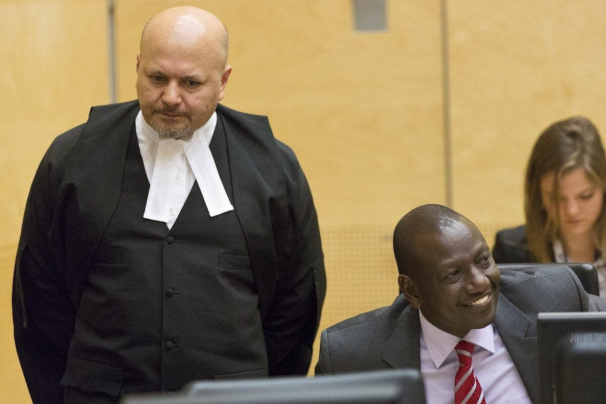 Defence counsel Karim Khan ( L) Kenya's Deputy President William Ruto (R) reacts as he sits in the courtroom before their trial at the International Criminal Court (ICC) in The Hague in 10 September 2013. [MICHAEL KOOREN/AFP via Getty Images]