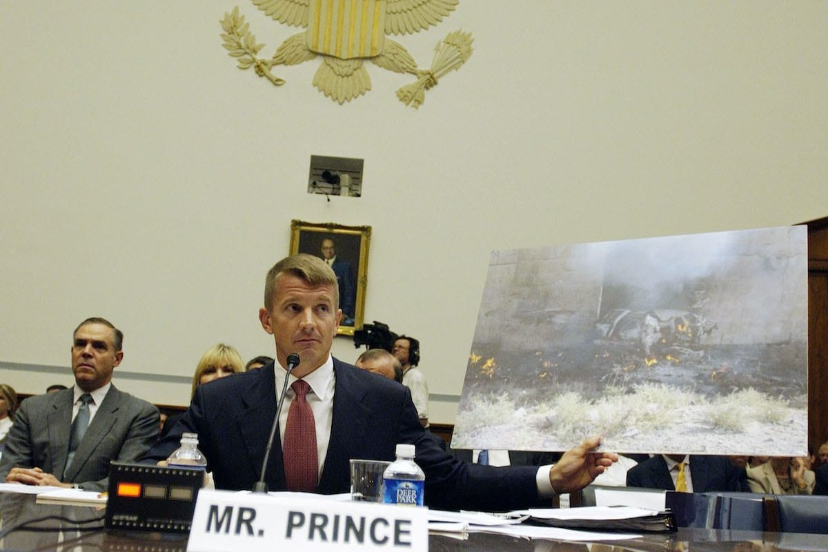 Erik Prince, Chairman, the Prince Group, LLC and Blackwater USA, holds up a picture of a Blackwater SUV hit by a suicide car bomb in Mosul, Iraq, in 2005, as he testifies during a hearing of the House Oversight and Government Reform Committee on Capitol Hill in Washington, D.C., private security contracting in Iraq and Afghanistan on 2 Oct. 2007. [Bill Putnam/Bloomberg via Getty Images]