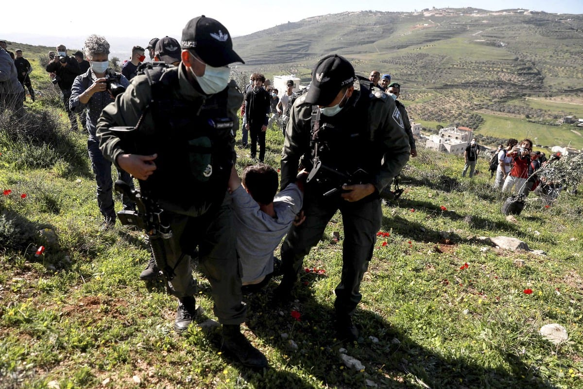Israeli soldiers arrest a demonstrator as Palestinians and foreign activists gathered to plant trees in a field that is under the risk of being seized by Israeli forces at the Burin village in southern Nablus, West Bank on 12 February 2021. [Issam Rimawi - Anadolu Agency]